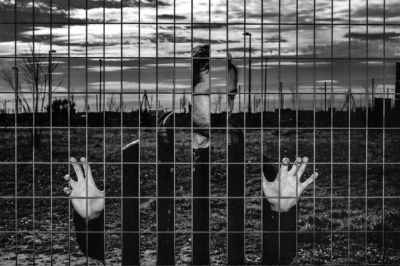 Artistic photo of a man trapped behind a fence