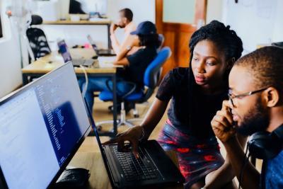 A woman helping a man at a computer